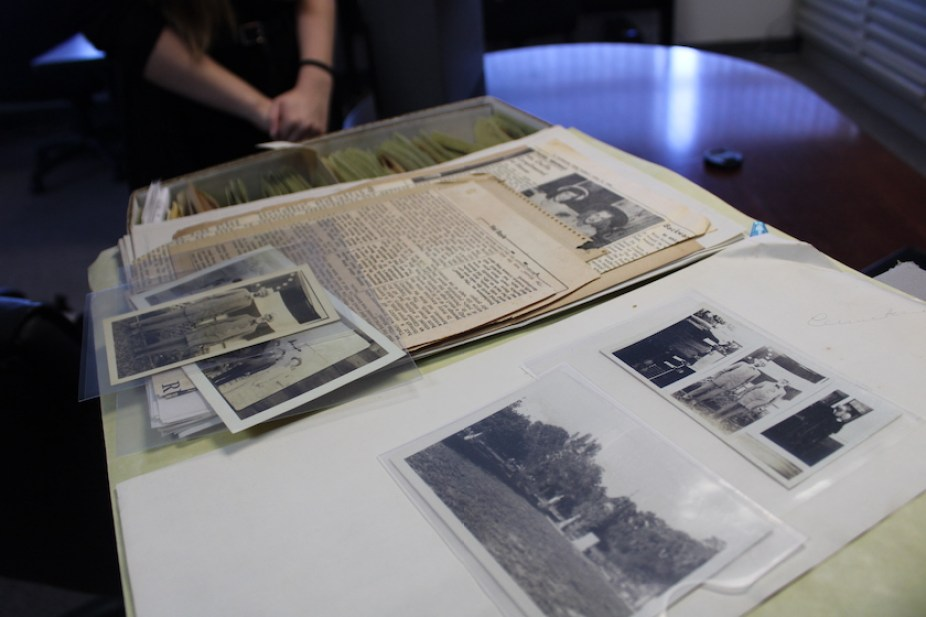 A table of old photos and newspaper articles in a museum.