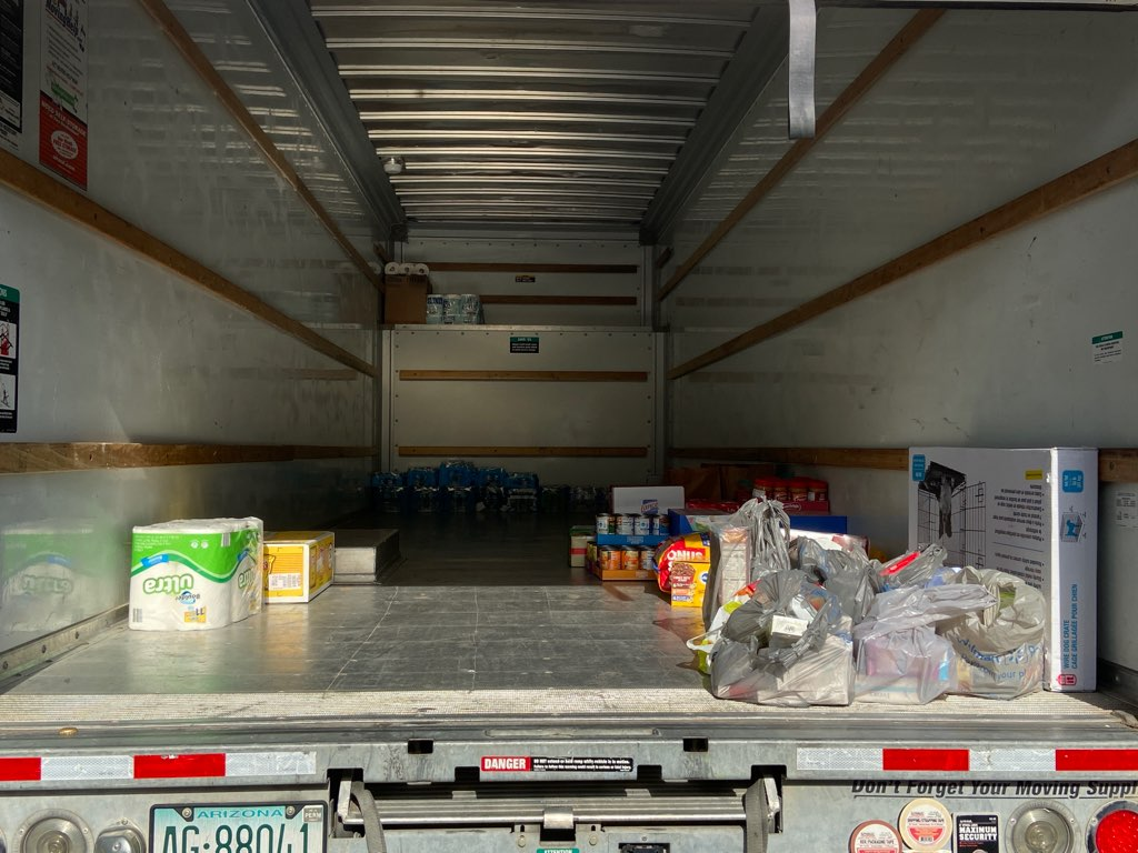 A photo of the inside of a cargo truck with a few food and cleaning supplies in it.