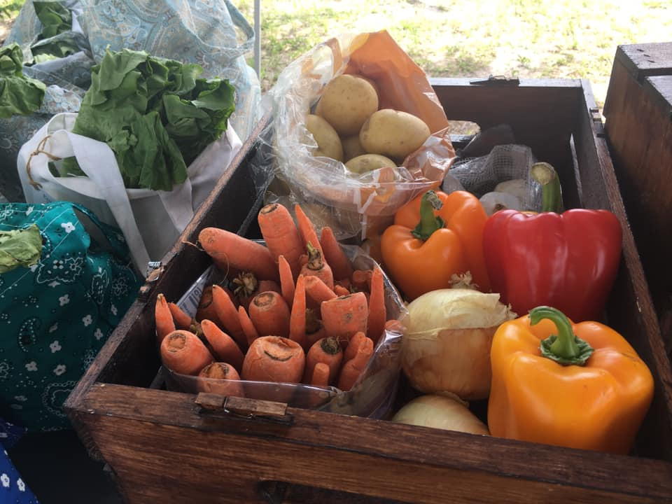 A photo of a wooden crate of produce in multiple colors.