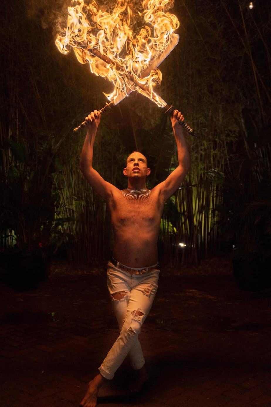 A photo of a man with no shirt and white pants performing with two sticks of fire crossed over his head.