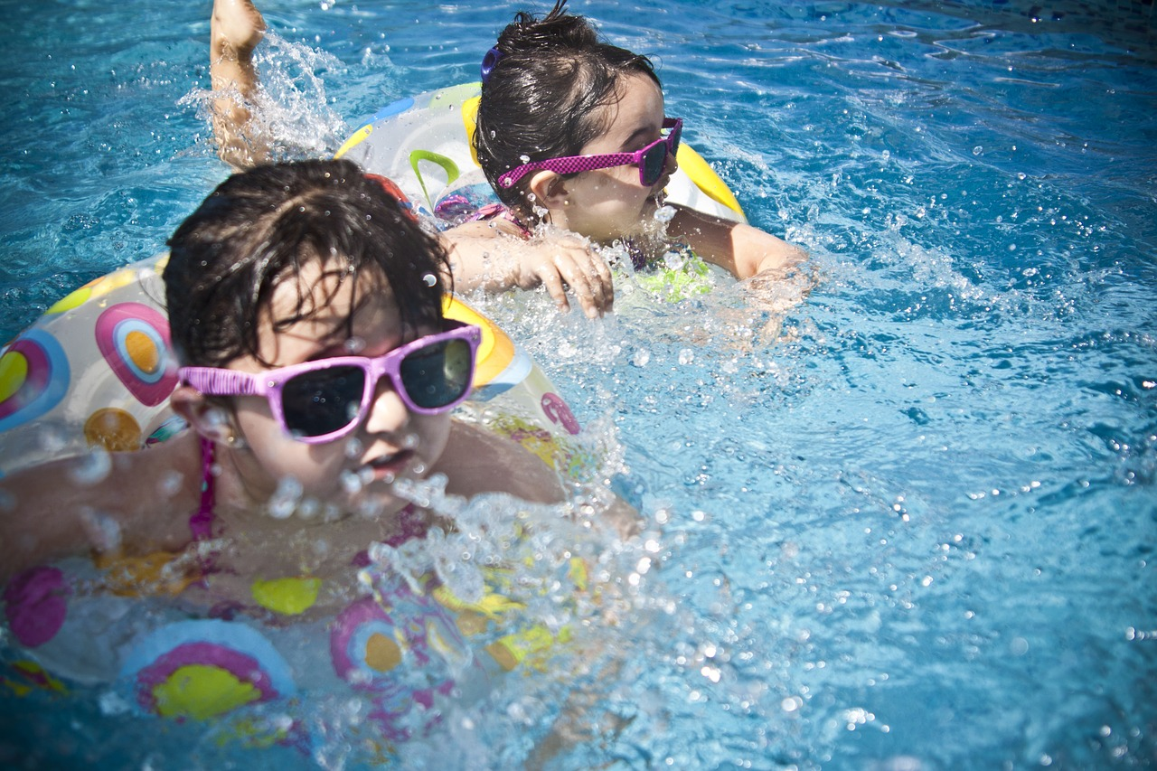 Two little kids in floats and sunglasses playing in a clear blue pool.