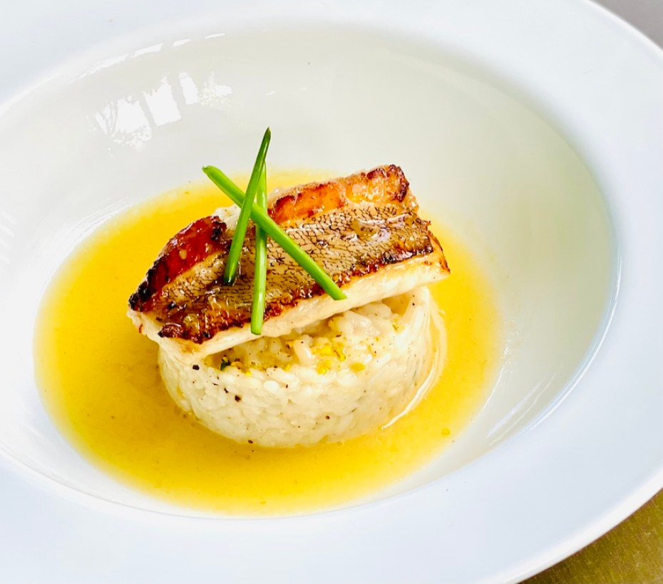 A dish of fish over a rice patty surrounded in a yellow sauce with chive garnish.