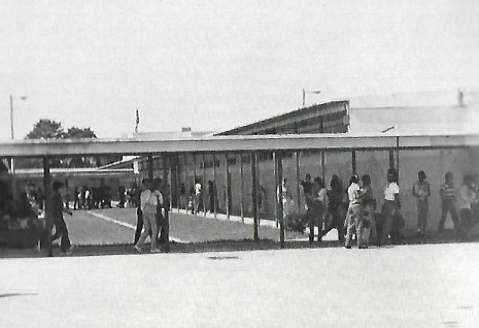 An old black and white photo of a high school corridor outdoors with students walking between buildings.