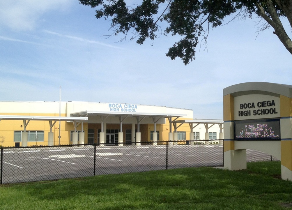 """A photo of a yellow and white high school building with a sign that reads """"Boca Ciega High School"""""""