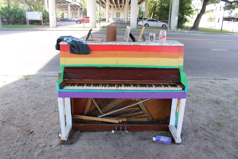 A rainbow-painted piano outside under a freeway overpass.