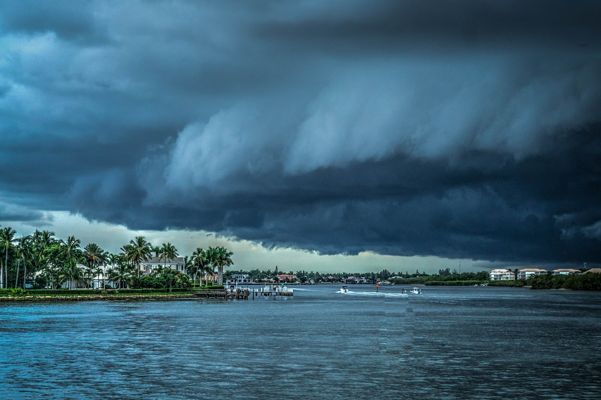 A large dark storm cloud moving over open water toward land with houses and palm trees.