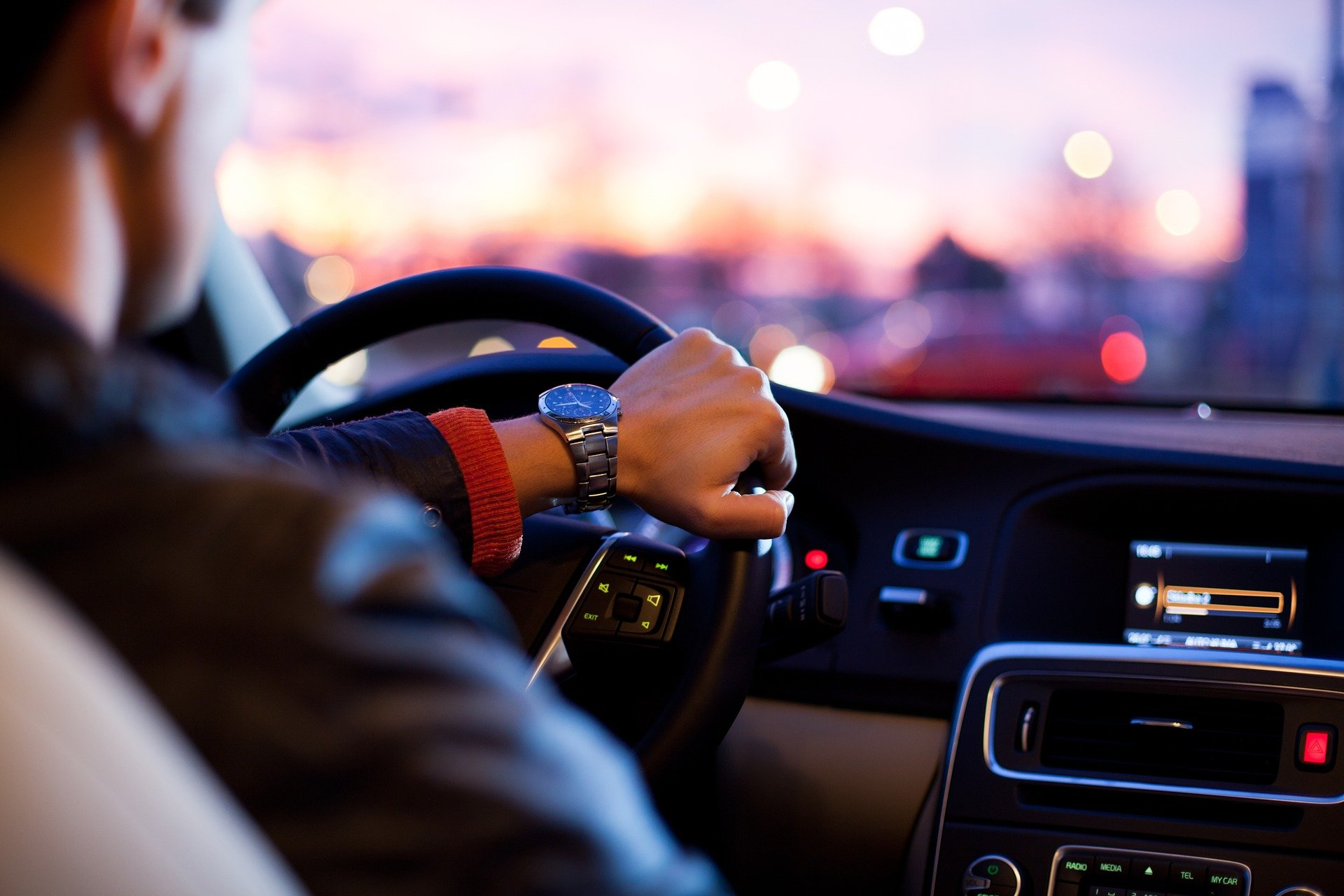 A photo of a man behind the wheel of a car at night with his hand on the steering wheel.