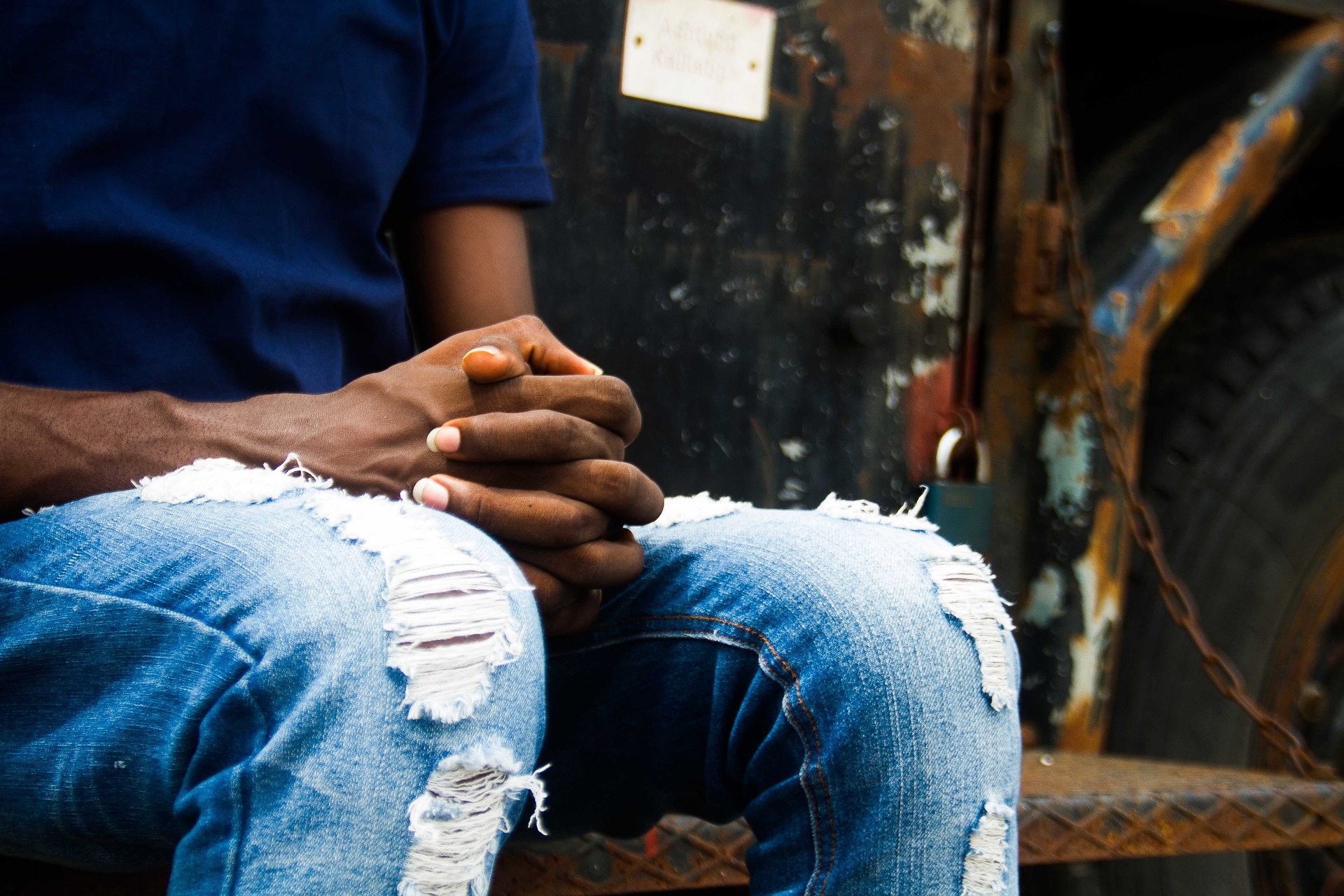 A photo of the lower half of a person sitting in a blue shirt and ripped jeans with hands folded in lap.