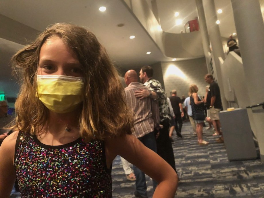 A photo of a young girl with a yellow face mask standing in a theater lobby.