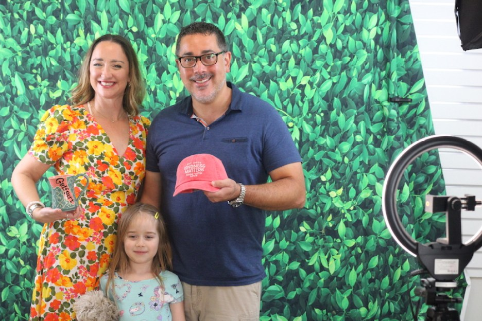 """A photo of a man holding a red cap that reads """"Kindness Matters"""", woman and little girl smiling at the camera in front of a green background."""