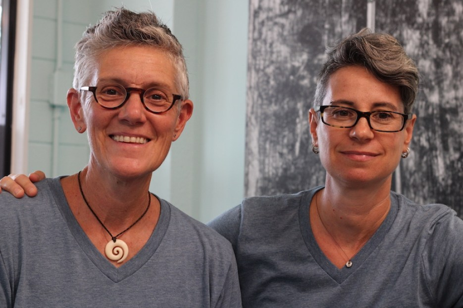 A photo of two women in glasses and gray t-shirts smiling at the camera.