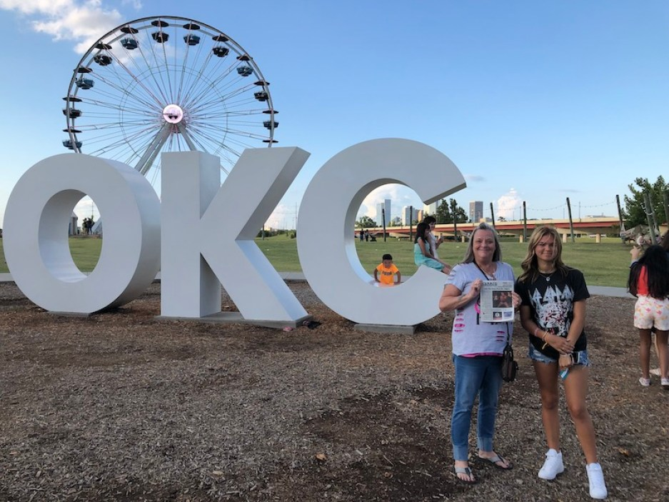 """A photo of a woman and a girl standing in front of giant """"OKC"""" letters outside, with a large ferris wheel in the background."""