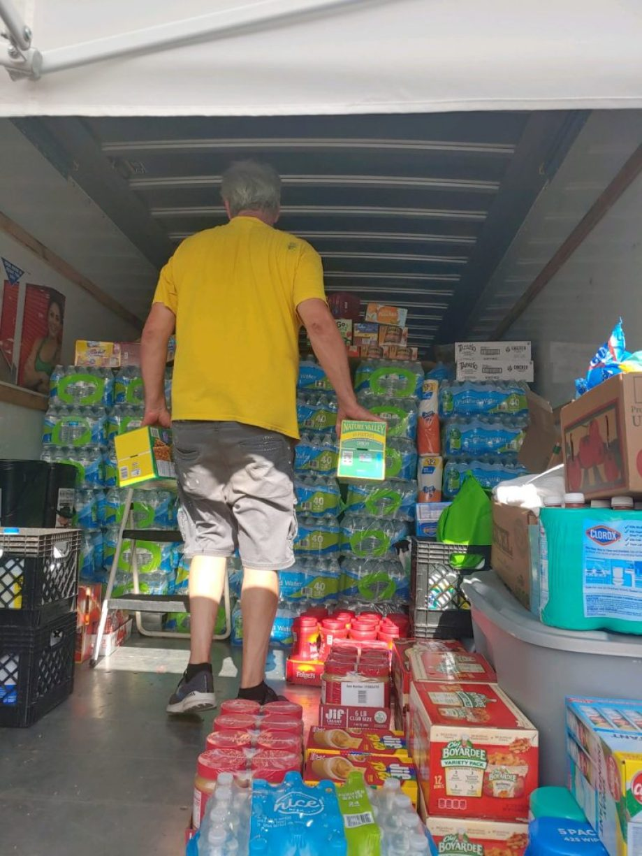 A photo of the back of a cargo truck packed full of supplies with the back of a man in a yellow t-shirt inside.