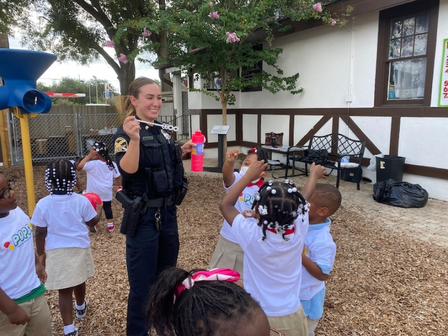 A woman in a black police officer's uniform playing with a group of small children on a playground.