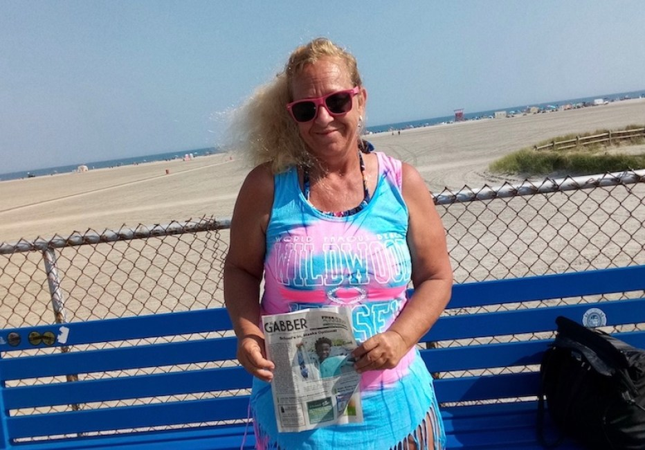 A photo of a woman in a colorful dress iat a beach boardwalk holding a copy of the Gabber Newspaper.