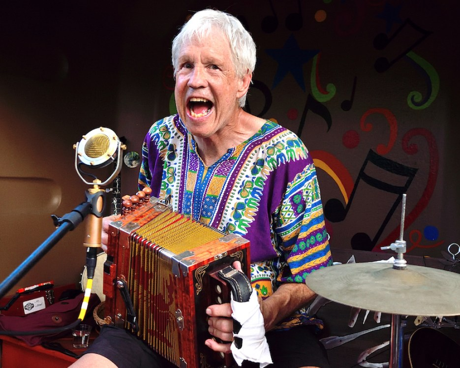A man in a multicolored shirt playing accordion and singing into a microphone.