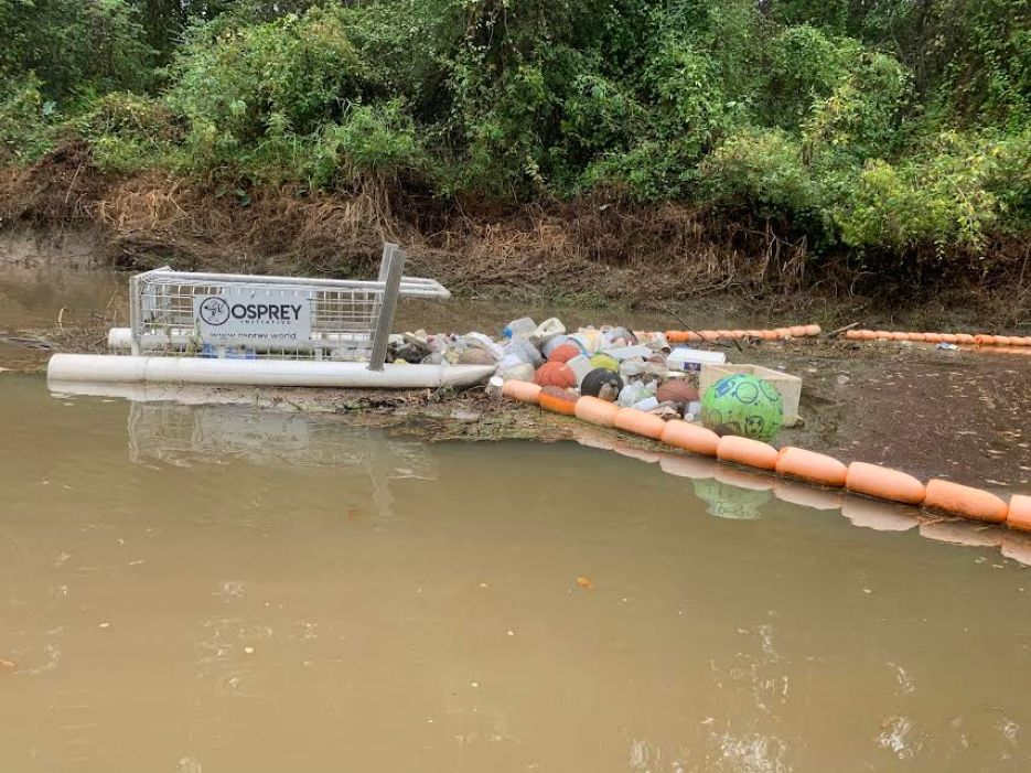 A photo of a trash-collecting device in murky water near land.