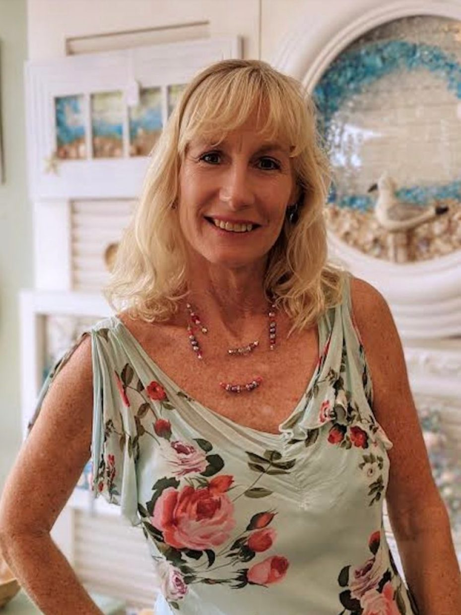 A blonde woman in a floral dress smiling at the camera.