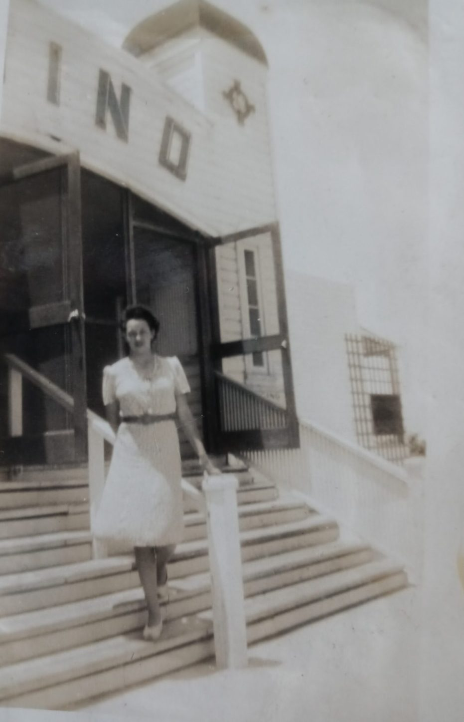 An old black and white photo of a woman standing on steps in front of a building in a white dress and dark belt.