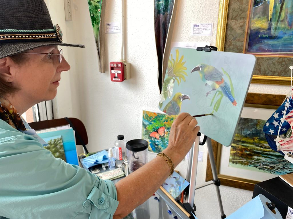 Woman in a black fedora painting on a canvas with a blue shirt on.