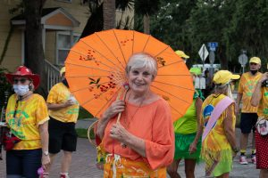 A photo of a woman smiling at the camera holding a large orange parasol outside at a street festival.