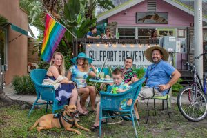 """A photo of a group of people in outdoor chairs with a dog in the foreground sitting outside of a house with a sign that reads """"Gulfport Brewery"""" next to a rainbow flag."""