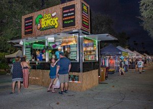"""A photo of people at a food stand at night on a street with a green sign that reads """"Bongo's"""""""