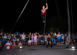 A photo of a street performer climbing a pole at a nighttime street festival as a crowd of people look on.
