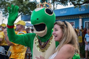 A photo of a woman standing next to a person dressed in a full, green lizard costume.