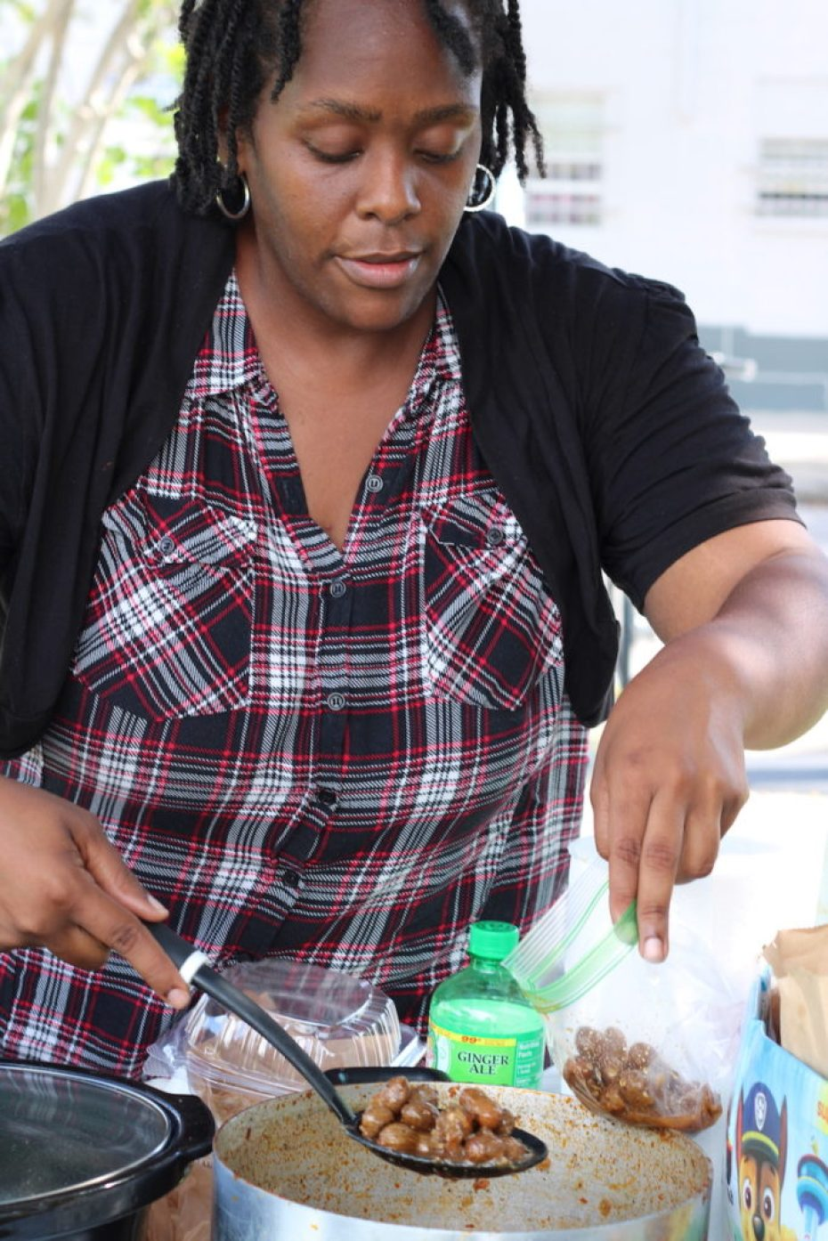 A photo of a woman in a plaid shirt and black sweater serving up a spoonful of boiled peanuts from a pot.