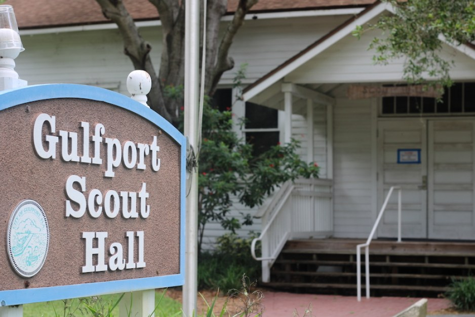 """A photo of a brown, blue and white sign that reads """"Gulfport Scout Hall"""" with an old white building in the background."""