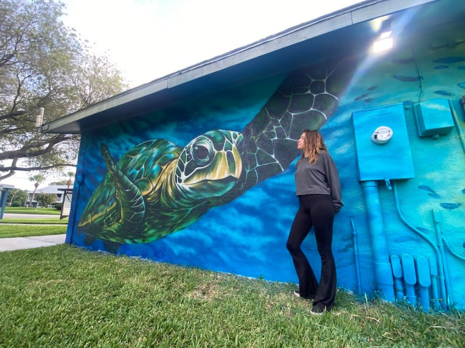 A woman standing next to a large mural on the side of a building featuring a sea turtle swimming in blue waters.