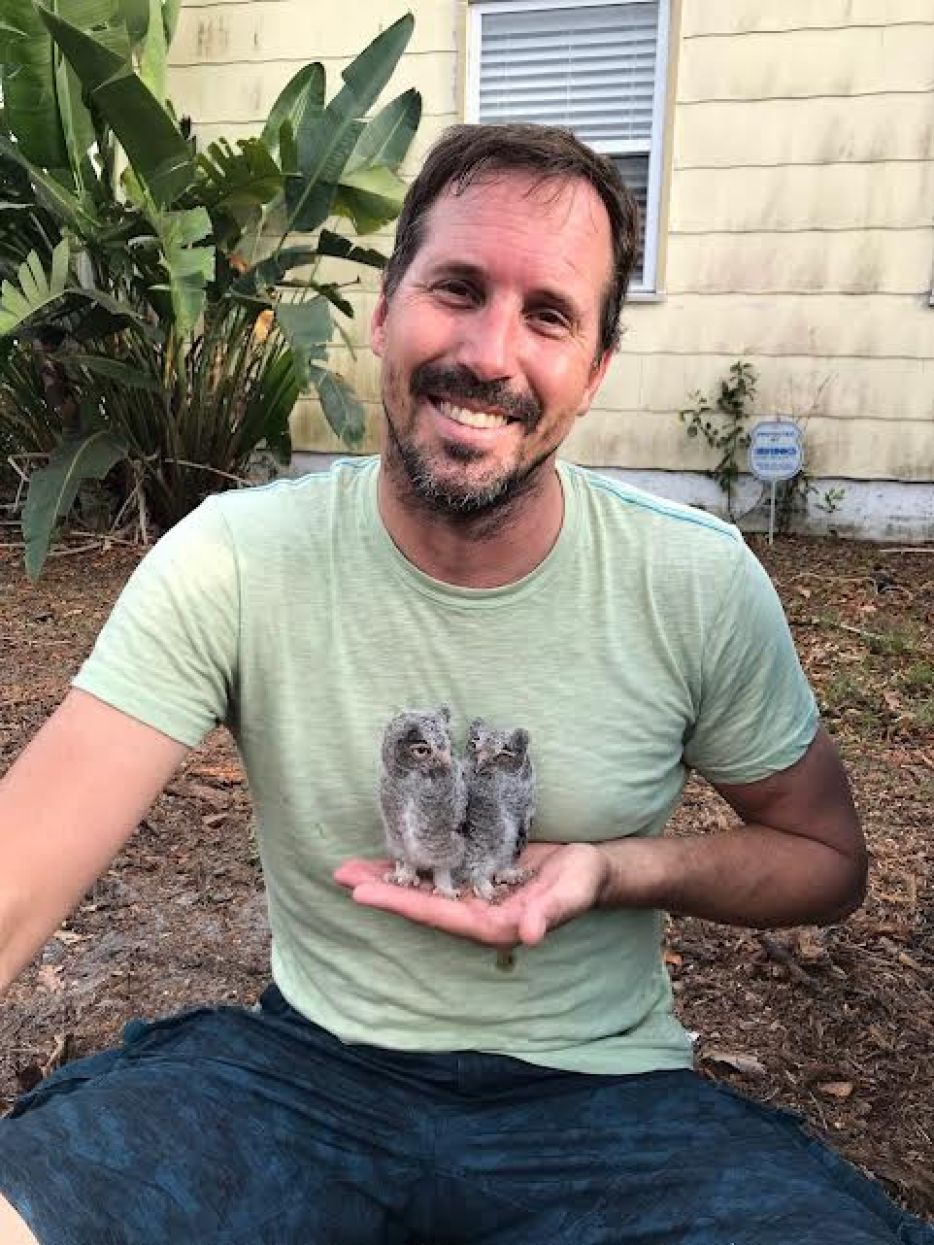 A photo of a man in a green t-shirt sitting outside a house holding two baby owls in the palm of his hand and smiling.
