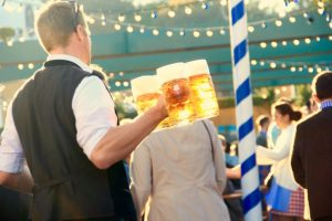 A man holding three mugs of beer and walking in a crowd