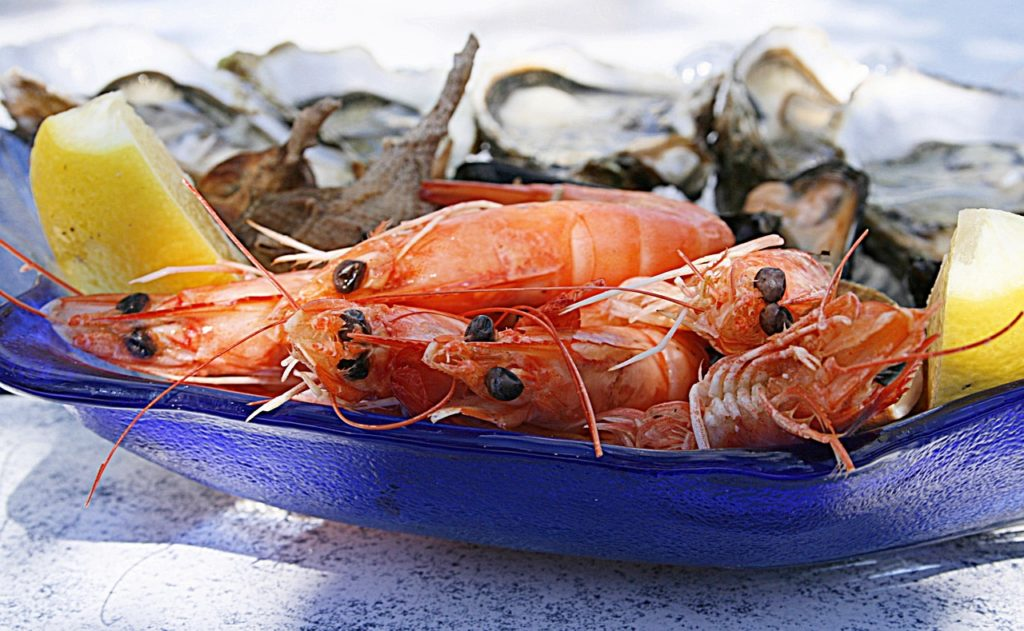 A plate of seafood with pink shrimps and lemon garnish