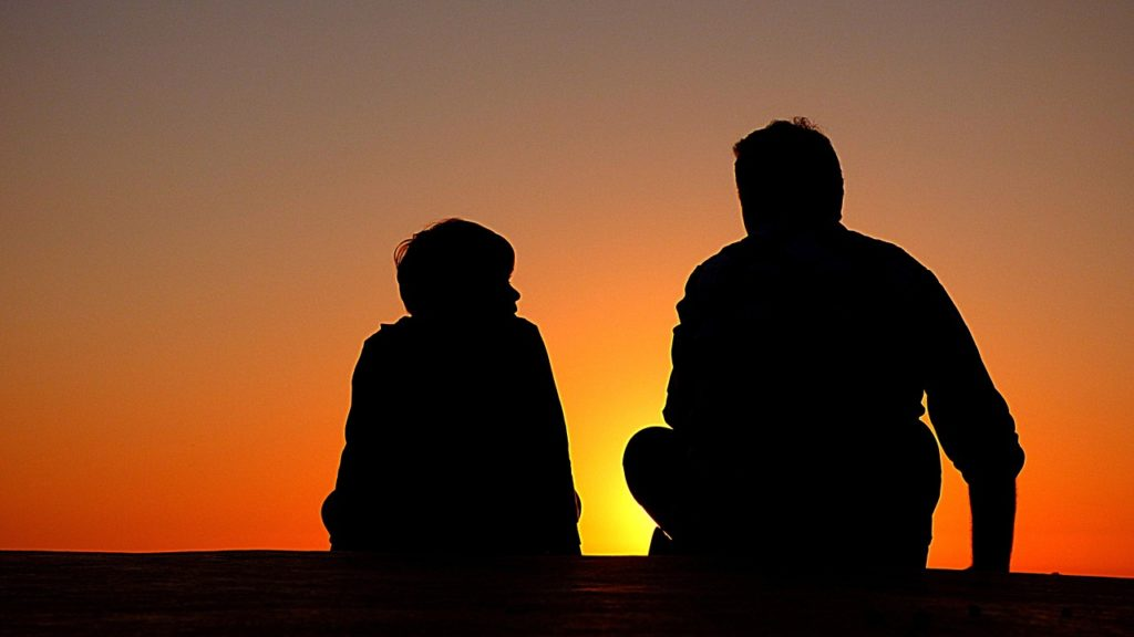 A silhouette of an adult and child in a sunset.