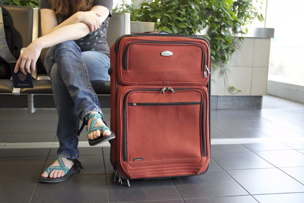 A photo of the bottom of a person sitting with a red suitcase on the ground next to them.