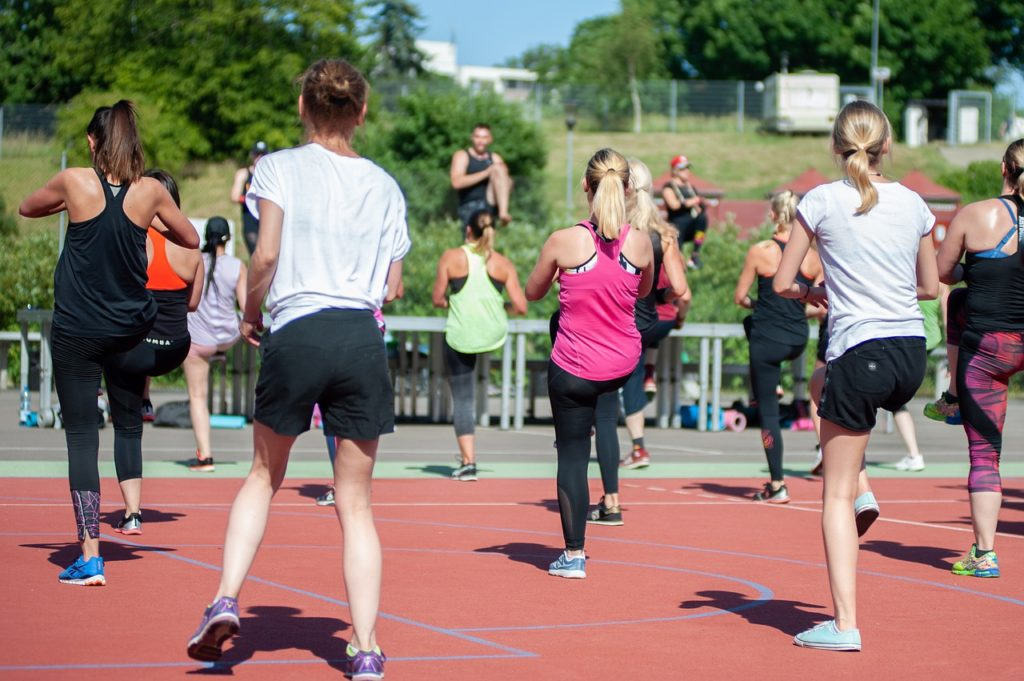 A photo of the backs of people participating in an exercise class outdoors.
