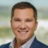 A headshot photo of a man smiling at the camera.