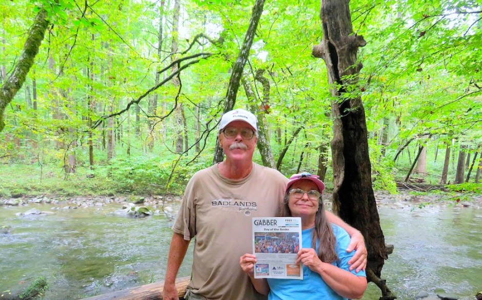 A photo of a man and a woman in a green wood holding a copy of the Gabber Newspaper