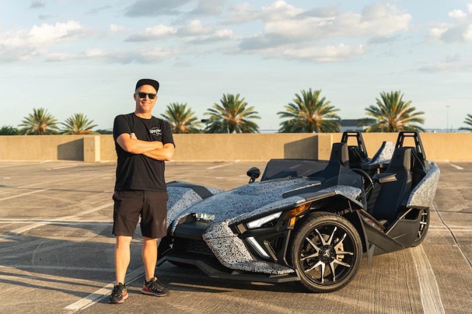 A photo of a man standing next to a black and gray Slingshot three-wheeled motorcycle on a rooftop parking garage.