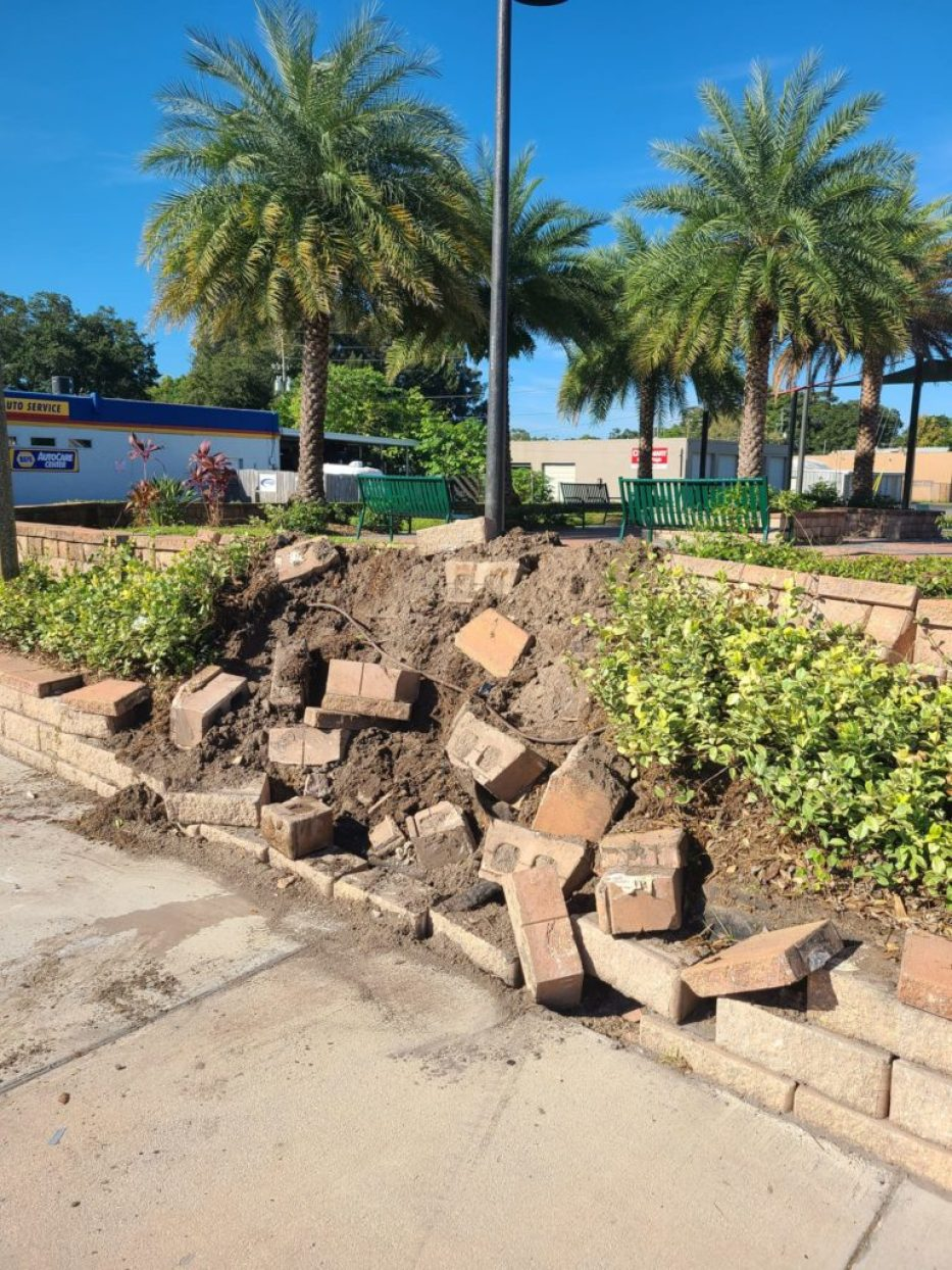 A photo of a paver wall at a park that has been partially demolished.