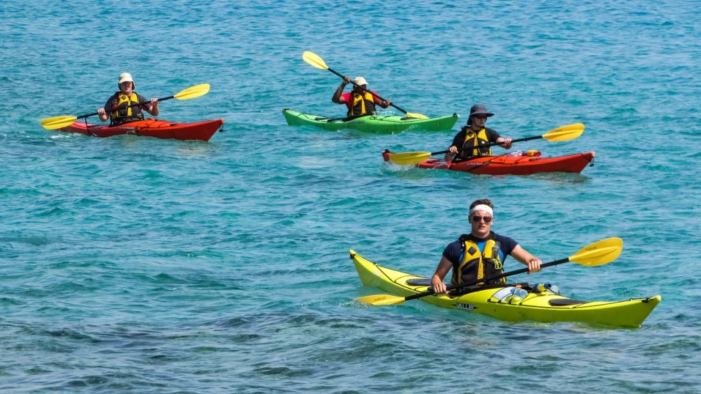 A group of four people in multicolored kayaks in the open water.