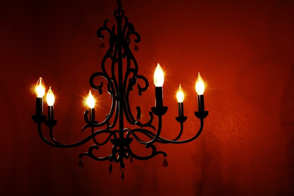 Chandelier with flames hanging in a red room