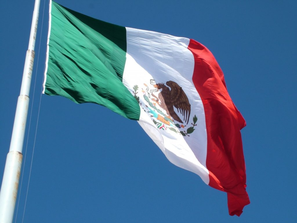 A red, white and green Mexican flag flying in the wind