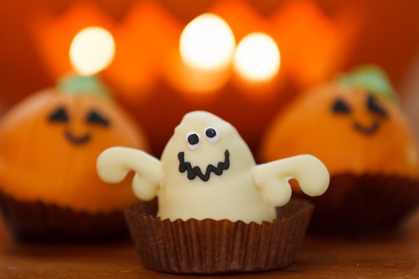 Three cupcakes, with a ghost cupcake in the front and two pumpkin cupcakes in the back