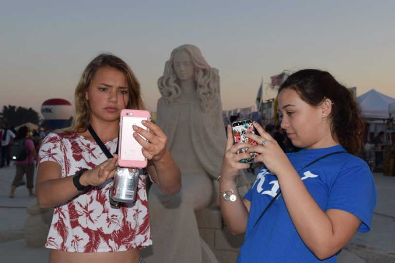 """Chloe Johnson, left, and Jessica Rogers, both of St. Petersburg, take selfies with a sand sculpture by artist Dmitry Klimenko of Moscow titled """"My Changing Woman"""" as the sun prepares to set Saturday Nov. 19 in Treasure Island. The piece won second place in the eighth annual Sanding Ovations Masters Cup Sand Sculpture Competition and Music Festival held Nov. 16-20. First place went to a piece titled """"Biological Link"""" by Jonathan Bouchard of Montreal, who also won first place in 2012, 2013 and 2014. """"We came here last year and the year before,"""" Johnson said of the event, which also included craft and food vendors. """"It's like a family tradition."""""""