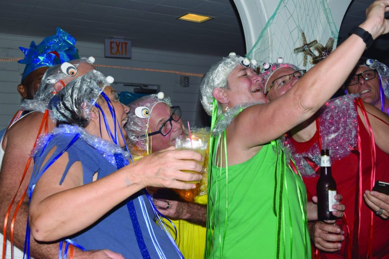 "Linda Breen of Gulfport, center, takes a group selfie of her ""pride"" of jellyfish at the Gecko Ball on Saturday, August 27. The pride included three couples, with each person wearing a different color of the rainbow. Linda's wife, Nora Reavis, left foreground, said they spent the entire afternoon making their costumes, which consisted of bubble wrap, ribbon, LED lights and funny eyeballs. Reavis noted that a group of jellyfish is really called a ""swarm"" but that the group preferred to call themselves a pride."