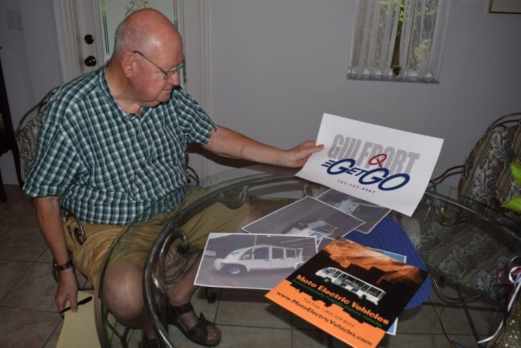 Bob Newcomb of Gulfport, who along with Biff Lagan is spearheading the Get-Go effort, shows off information about the shuttle manufacturer and the program's logo at his house on Friday, July 1.