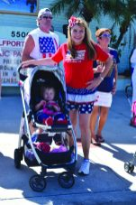 """Lisa Kauffman of Gulfport, dressed in her patriotic best, with her daughter Dreama, 1, wait for the parade to start. """"The Fourth of July was a little loud. That's why we have the ear guards,"""" Kauffman said of the pink sound mufflers Dreama was holding."""
